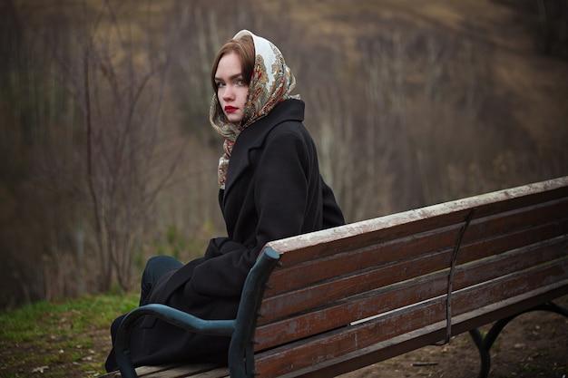 Jonge mooie vrouw zit op een bankje in de herfst in de natuur en kijkt over haar schouder.
