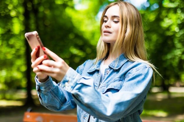 Jonge mooie vrouw zit op een bankje in het park, controleert de telefoon. buitenshuis.