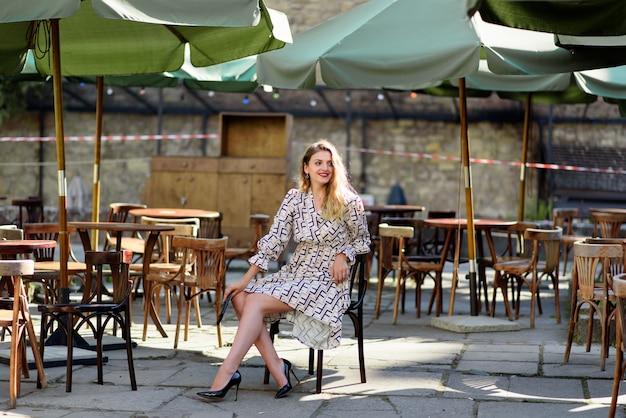 Jonge mooie vrouw zit op een stoel op het terras van een restaurant.
