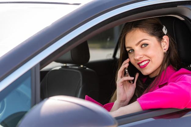 Jonge, mooie vrouw zitten achter het stuur van een auto en praten over de telefoon