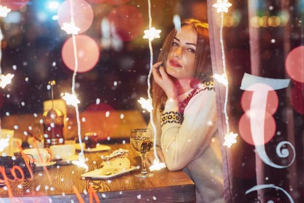 Jonge mooie vrouw zitten in café, het drinken van wijn. kerstmis, nieuwjaar, valentijnsdag, wintervakantie