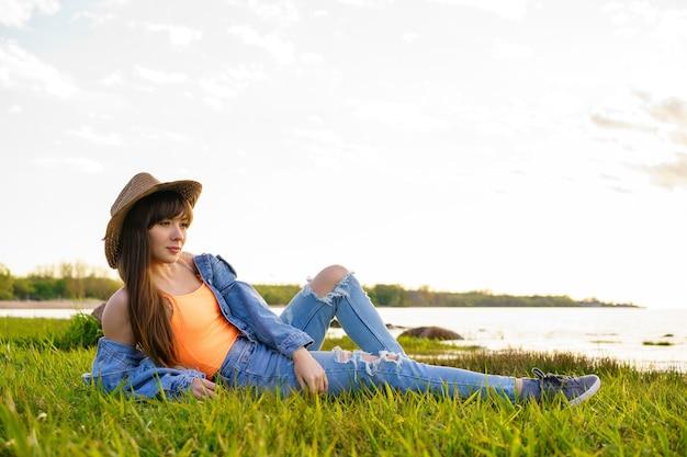 Jonge mooie vrouw zitten in een cowboyhoed op de baai in een denim pak bij zonsondergang
