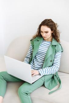 Jonge mooie vrouw zitten met laptop via internet