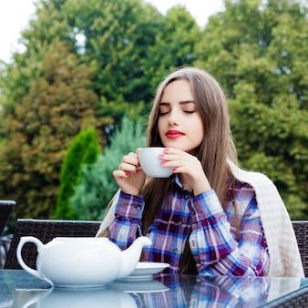 Jonge mooie vrouw zittend aan een tafel op het terras, inhaleert aroma van thee