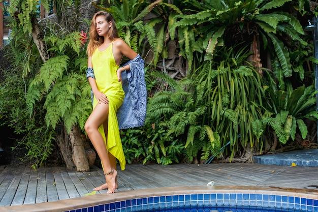 Jonge mooie vrouw zittend aan het zwembad in gele boho-jurk, zomertrendmode, sexy, mager, gebruinde huid, slanke benen, tropische vakantie, resorthotel, glimlachen, sensueel, reizen in azië, heet,