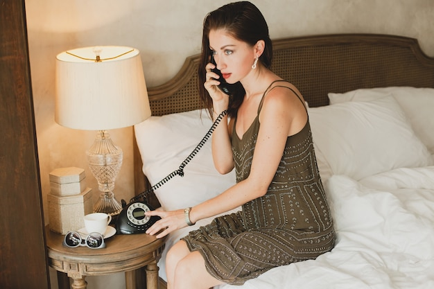 Jonge mooie vrouw zittend op bed in hotel, stijlvolle avondjurk, sensuele stemming, praten aan de telefoon, glimlachen, flirterig, kijken, sexy