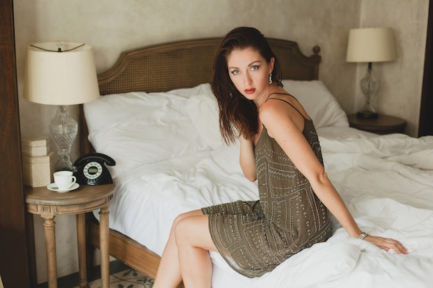 Jonge mooie vrouw zittend op bed in hotelkamer, stijlvolle avondjurk, flirterige, sexy, mode-outfit, witte lakens