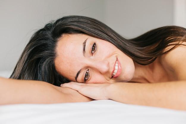 Jonge mooie vrouw zittend op bed, rusten en glimlachen. lifestyle thuis. binnenshuis. portret