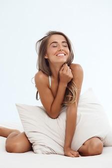 Jonge mooie vrouw zittend op bed vroeg in de ochtend