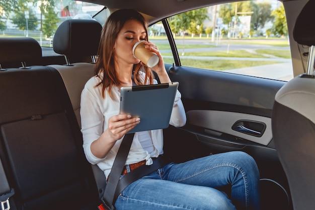Jonge mooie vrouw zittend op de achterbank van de auto