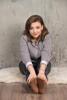 Jonge mooie vrouw zittend op de vloer en kijkend naar de voorkant