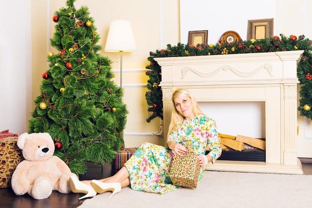 Jonge mooie vrouw zittend op de vloer in de buurt van de kerstboom en presenteert op een nieuwe jaar vooravond. interieur met kerstversiering.