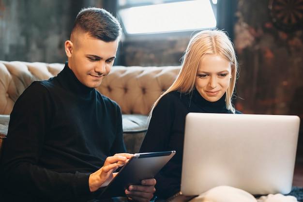 Jonge mooie vrouw zittend op de vloer tijdens het kijken naar haar laptop terwijl zijn vriendje naar een tablet kijkt