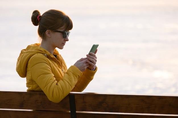 Jonge mooie vrouw zittend op een bankje in het park bladeren door haar sellphone buiten in de avond.