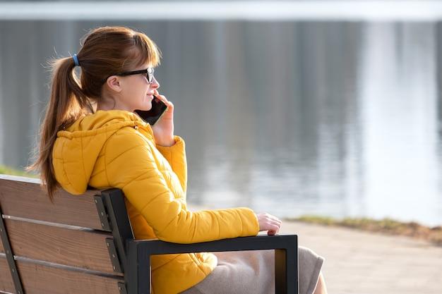 Jonge mooie vrouw zittend op een bankje in het park praten op haar smartphone buiten in de herfstavond