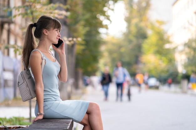Jonge mooie vrouw zittend op een bankje op straat praten op haar smartphone buiten in warme zomerdag.