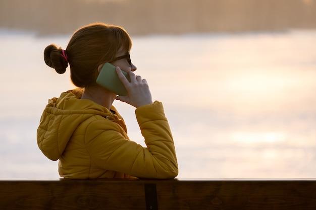 Jonge mooie vrouw zittend op een bankje praten op haar mobiele telefoon buiten in de avond.