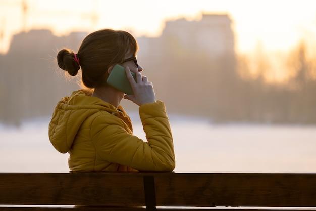 Jonge mooie vrouw zittend op een bankje praten op haar smartphone buiten in warme herfstavond.
