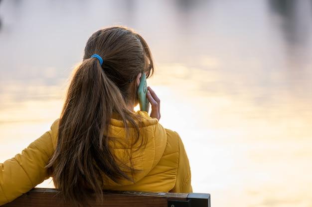 Jonge mooie vrouw zittend op een bankje praten op haar smartphone buitenshuis.