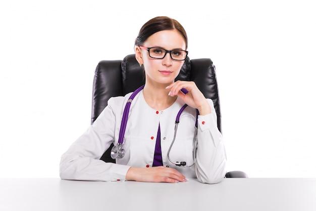 Jonge mooie vrouwelijke artsenzitting in haar werkende plaats die op patiënt op wit wacht