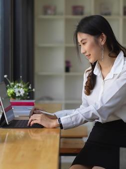 Jonge mooie vrouwelijke beambte die met digitale tablet werkt