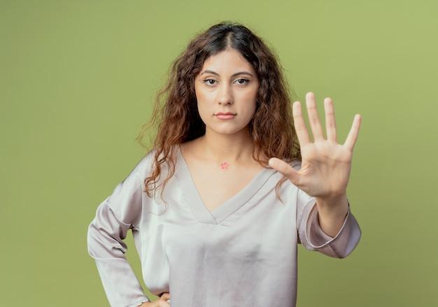 Jonge mooie vrouwelijke beambte die stopgebaar toont en hand op heup zet die op olijfgroene muur wordt geïsoleerd