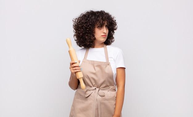 Jonge mooie vrouwelijke chef-kok die zich verdrietig, boos of boos voelt en naar de kant kijkt met een negatieve houding, fronsend van onenigheid