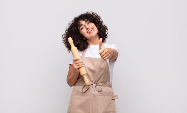 Jonge mooie vrouwelijke chef-kok voelt zich trots, zorgeloos, zelfverzekerd en gelukkig, positief glimlachend met duimen omhoog