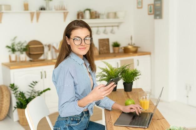 Jonge mooie vrouwelijke freelancer die thuis werkt tijdens quarantaine