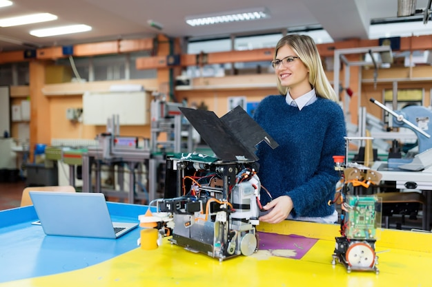Jonge mooie vrouwelijke ingenieur test robot bij robotica-ontwikkeling