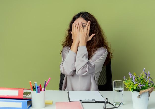 Jonge mooie vrouwelijke kantoormedewerker zit aan bureau