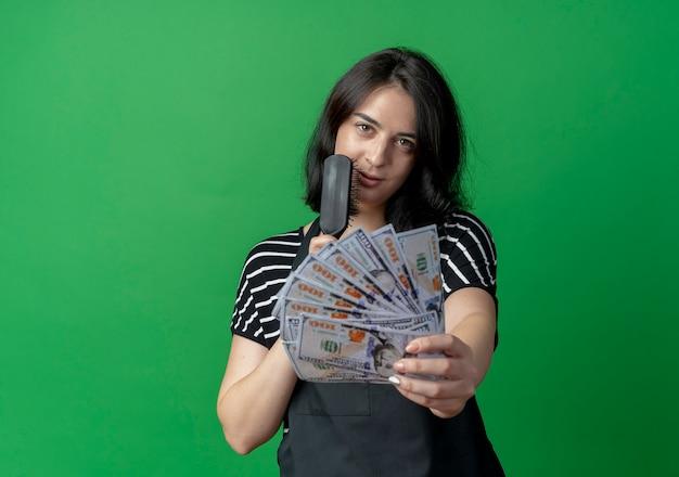 Jonge mooie vrouwelijke kapper die in het haarborstel van de schortholding contant geld toont dat zelfverzekerd over groene muur glimlacht