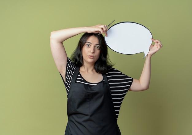 Jonge mooie vrouwelijke kapper die in schort het lege teken van de toespraakbel boven het hoofd houdt verward status over lichte muur
