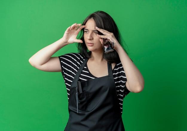 Jonge mooie vrouwelijke kapper die in schort opzij kijkt verward over groen