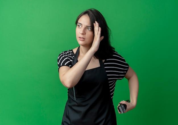 Jonge mooie vrouwelijke kapper die in schort opzij met hand dichtbij trimeer van de gezichtsholding kijkt die zich over groene muur bevindt