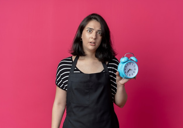 Jonge mooie vrouwelijke kapper die in schort wekker toont bezorgd die zich over roze muur bevindt