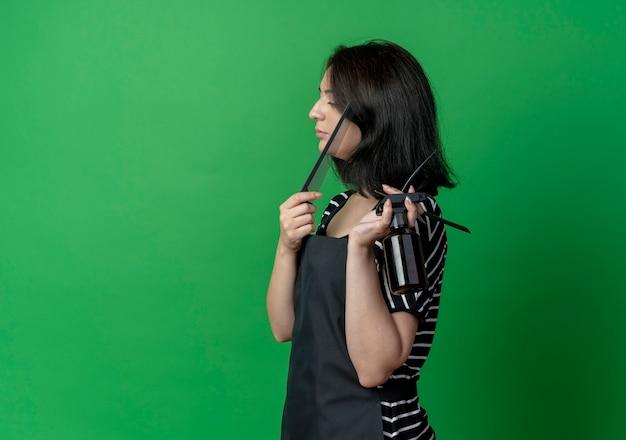 Jonge mooie vrouwelijke kapper die in schortstand zijdelings kamnevel en scheermes houdt over groene muur