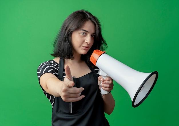 Jonge mooie vrouwelijke kapper in schort die met megafoon spreekt die met vinger naar camera richt die over groen kijkt vertrouwen