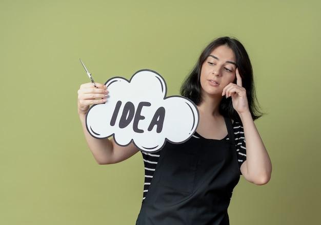 Jonge mooie vrouwelijke kapper in schort met schaar en lege tekstballon bord met idee woord kijken verbaasd staande over lichte muur