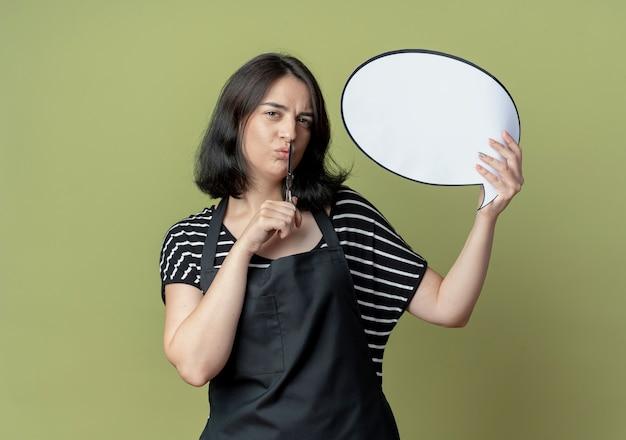 Jonge mooie vrouwelijke kapper in schort met schaar leeg tekstballon bord met zelfverzekerde uitdrukking staande over lichte muur