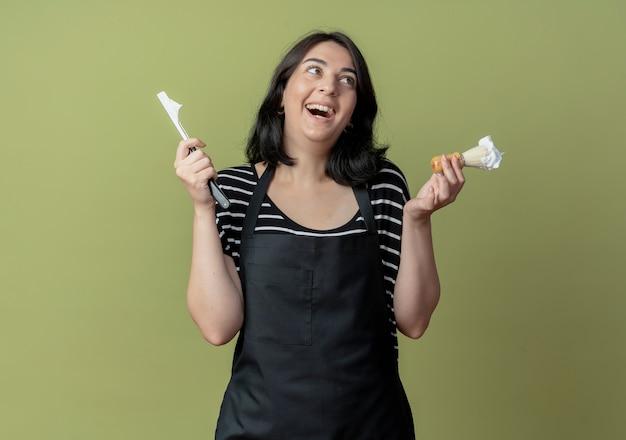 Jonge mooie vrouwelijke kapper in schort met scheermes en scheerkwast met schuim glimlachend vrolijk met blij gezicht staande over lichte muur