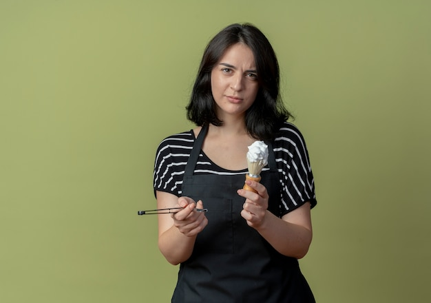 Jonge mooie vrouwelijke kapper in schort met scheermes en scheerkwast met schuim met ernstig gezicht staande over lichte muur