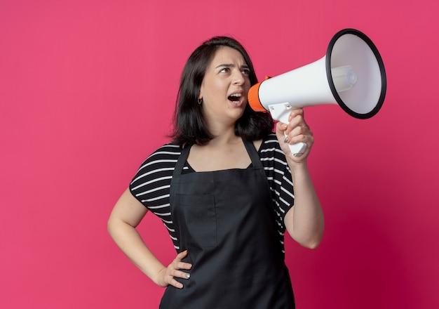 Jonge mooie vrouwelijke kapper in schort schreeuwen naar megafoon over roze