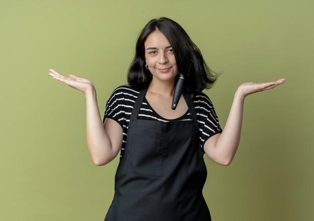 Jonge mooie vrouwelijke kapper in schort witg trimmer vast in haar haar verward armen naar de zijkanten spreiden over licht