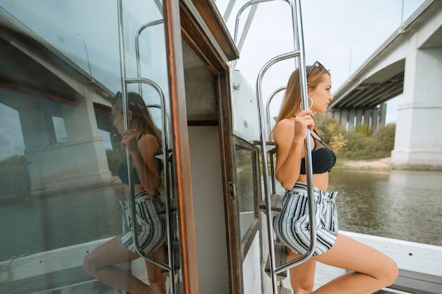 Jonge mooie vrouwelijke model op het dek van een jacht op zee. reizen en zeilen concept. luxe reizen op het jacht. jonge vrouw die geniet van mezelf op het bootdek dat de zee vaart.