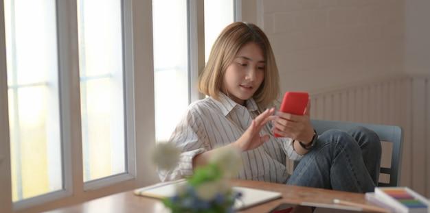 Jonge mooie vrouwelijke ontwerper die smartphone bekijkt en op de stoel zit