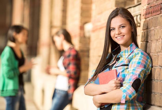 Jonge mooie vrouwelijke student aan de universiteit.