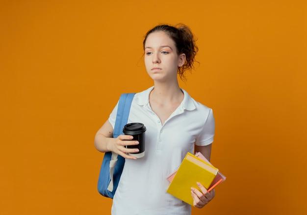 Jonge mooie vrouwelijke student die achterzak draagt die de pen van het de notitieblok van de zijholding en plastic koffiekop bekijkt die op oranje achtergrond met exemplaarruimte wordt geïsoleerd