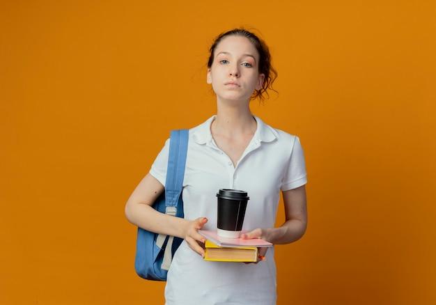 Jonge mooie vrouwelijke student die achterzak draagt die het stootkussenpen van de cameraholding bekijkt en plastic koffiekop op oranje achtergrond met exemplaarruimte wordt geïsoleerd