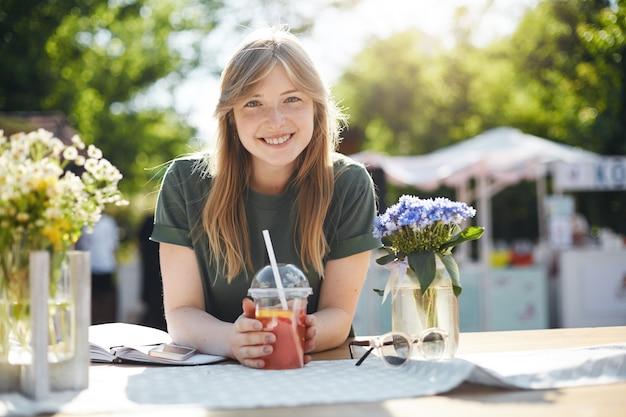 Jonge mooie vrouwelijke student die een pauze neemt van klassen die grapefruitlimonade het glimlachen drinken